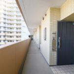共用廊下は余裕がある幅があります。玄関前にはウェルカムコート(タイル部分)があります。(玄関)