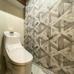 洗浄便座一体型トイレ。上部には収納があります。壁紙にはシックなデザインクロスを採用しました。(内装)