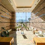 天井が高く開放的なエントランスホール。石貼りの壁面が印象的です。(周辺)