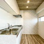 キッチンの背面には窓があります。換気がしやすいキッチンです。壁面には印象的なアクセントクロスを施工。(キッチン)